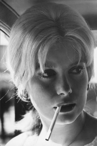 """Tournage du film """"Un monsieur de compagnie"""" de Philippe DE BROCA : plan de trois-quarts de Catherine DENEUVE une cigarette à la bouche, dans une voiture"""