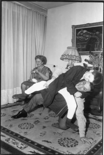 En famille dans leur appartement du XVIe arrondissement à PARIS : dans le salon Lino VENTURA assis sur le tapis jouant avec son fils Laurent (8 ans) ce dernier en peignoir essayant d'étrangler son père avec le bras lors d'une partie de catch sa mère Odette (souriante) tricotant en arrière plan assise dans un fauteuil.