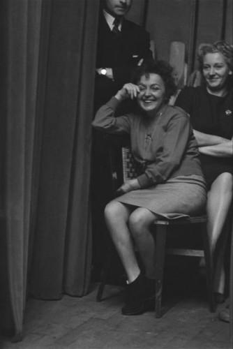 Edith PIAF, assise en coulisse derrière le rideau, souriante.