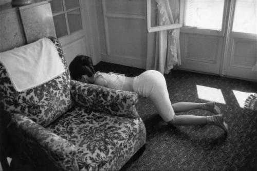Nathalie WOOD parre terre à quattre pattes derrière un fauteuil dans sa chambre d'hôtel à Cannes en 1962.