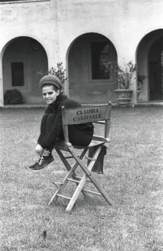 Claudia CARDINALE chez elle dans sa nouvelle propriété, la villa Santa Anna di Malborghetto, une ancienne ferme, sur la Via Flaminia près de Rome : la comédienne coiffée d'un bonnet posant assise sur une chaise pliante à son nom dans son jardin jouxtant la maison.