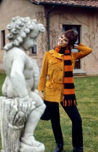 Claudia CARDINALE chez elle dans sa nouvelle propriété, la villa Santa Anna di Malborghetto, une ancienne ferme, sur la Via Flaminia près de Rome : Claudia dans son jardin d'été, souriante, posant près de la statue en pierre d'un Amour, sa maison en arrière plan.