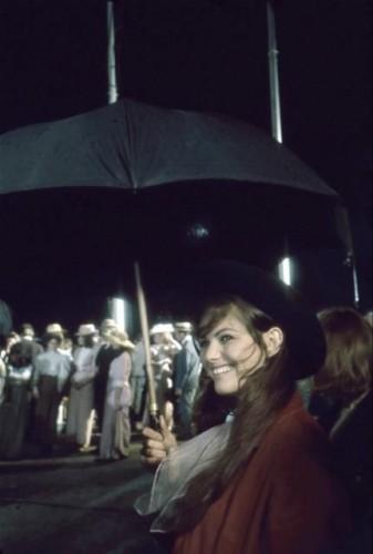 """Le film """"Le PLUS GRAND CIRQUE DU MONDE"""" de Henry Hathaway tourné en ESPAGNE : sur le tournage, Claudia CARDINALE souriante, se protégeant avec un parapluie."""