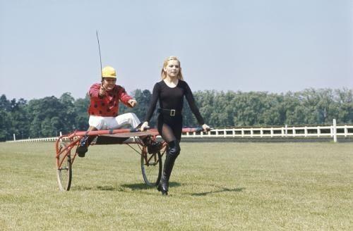 Attitude de France GALL en body noir et cuissardes sur un champ de course tirant un sulky sur lequel est assis un jockey tenant une cravache.
