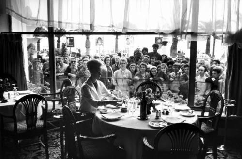 Tippi HEDREN assise seule à une table ronde et prenant un verre. Hitchcock lui avait appris à se tenir à table et à contenir ses émotions au point d'en paraître glacée. Cannes 1969