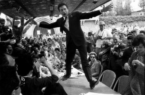 Jean-Pierre CASSEL improvise un pas de danse sur la table de la mère Terrat à la Napoule lors du Festival de Cannes 1960.