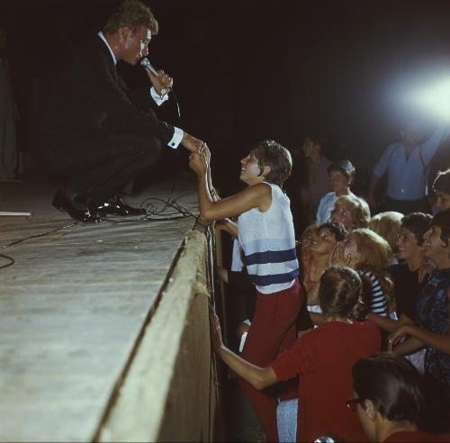 """Johnny HALLYDAY en tournée. Au théâtre du Pharo à Marseille, pendant tout le temps qu'il chante """"On m'appelle l'idole des jeunes"""", une jeune fille de 16 ans, extasiée, lui tient la main. C'est une fan type. Elle possède tous les disques de son idole."""