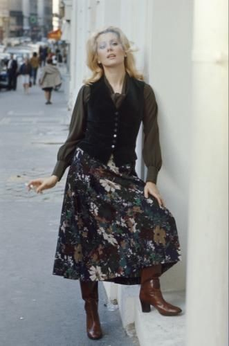 Catherine DENEUVE présente la mode Yves SAINT LAURENT rue de Tournon à PARIS chez SAINT LAURENT Rive Gauche : attitude souriante de l'actrice posant dans la rue en kilt fleuri et blouse de soie verte sur gilet de velours marron, recrachant la fumée de la cigarette qu'elle tient à la main.