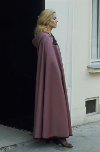 Catherine DENEUVE présente la mode Yves SAINT LAURENT rue de Tournon à PARIS chez SAINT LAURENT Rive Gauche : plan de profil de l'actrice posant dans une cour d'immeuble en longue cape lilas.