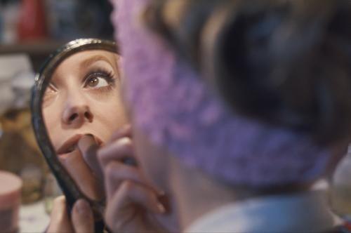"""Catherine DENEUVE un bandeau rose autour de la tête, de dos, se mettant du rouge à lèvres entre deux plans sur le tournage du film """"Manon 70"""" de Jean AUREL, son reflet dans un miroir de courtoisie."""