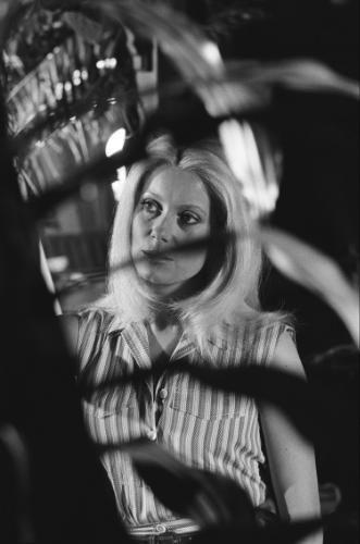 """Plan de trois-quarts de Catherine DENEUVE derrière du feuillage sur le tournage du film """"Le sauvage"""" de Jean-Paul RAPPENEAU."""