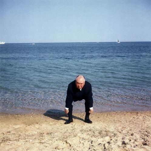 """A Cannes pour présenter son film """"Les Oiseaux"""", attitude d'Alfred HITCHCOCK imitant la démarche pataude d'une mouette au bord de l'eau, sur une plage."""
