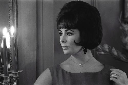 """Elizabeth TAYLOR s'arrête quelques jours à PARIS après avoir quitté Londres avant de rejoindre les Etats-Unis pour se reposer après son opération en plein tournage de """"Cléopâtre"""" : plan de trois-quarts de l'actrice dans l'appartement 72, """"la suite de luxe"""", de l'hôtel Lancaster à PARIS, éclairée par des bougies posées sur le manteau de"""