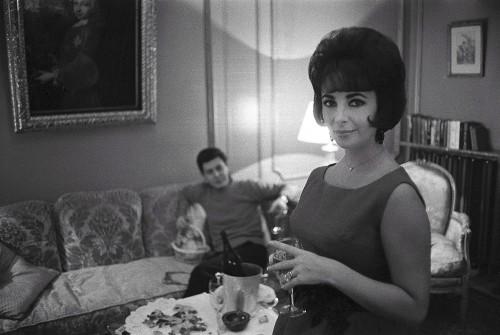 """Elizabeth TAYLOR s'arrête quelques jours à PARIS après avoir quitté Londres avant de rejoindre les Etats-Unis pour se reposer après son opération en plein tournage de """"Cléopâtre"""" : plan de face souriant de l'actrice debout dans l'appartement 72, """"la suite de luxe"""", de l'hôtel Lancaster à PARIS, un verre de champagne Dom Pérignon à la main, son mari Eddie FISHER assis sur le canapé en"""