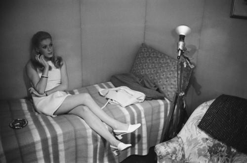 """Attitude de Catherine DENEUVE les cheveux tirés en arrière, fumant une cigarette assise sur un lit sur le tournage du film """"Manon 70"""" de Jean AURE"""