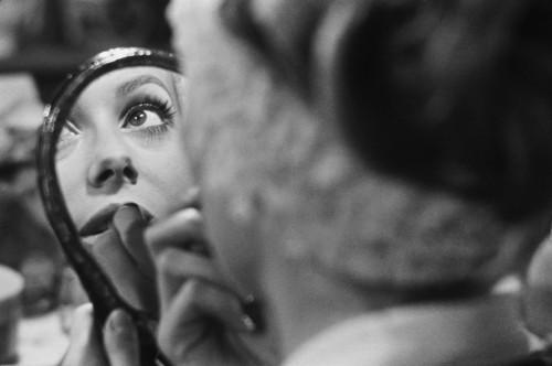 """Catherine DENEUVE de dos, un bandeau autour de la tête, se mettant du rouge à lèvres entre deux plans sur le tournage du film """"Manon 70"""" de Jean AUREL, son reflet dans un miroir de courtois"""