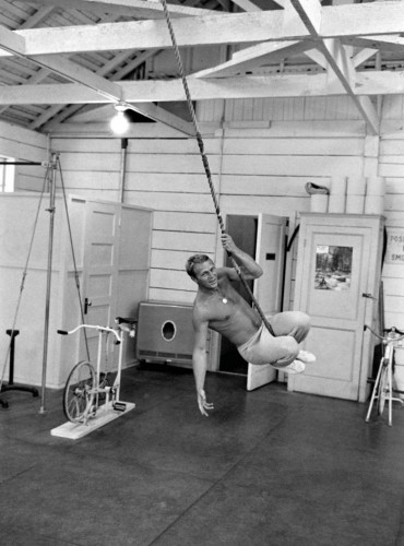 Steve McQueen swinging from rope at gym