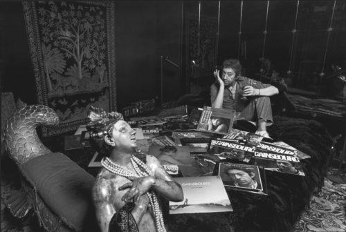 Gainsbourg sur son lit, entouré de quelques-uns de ses albums souvent illustrés par des photos de Tony Frank, 1979